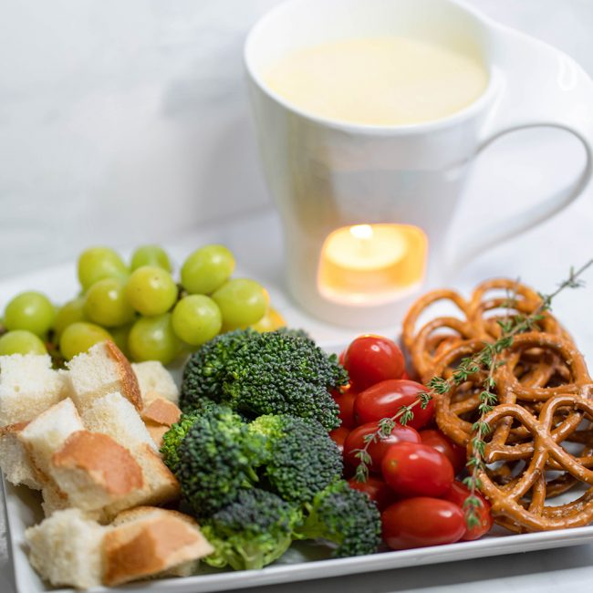 Swiss cheese fondue withwith bread cubes, broccoli, cherry tomatoes, and pretzels.